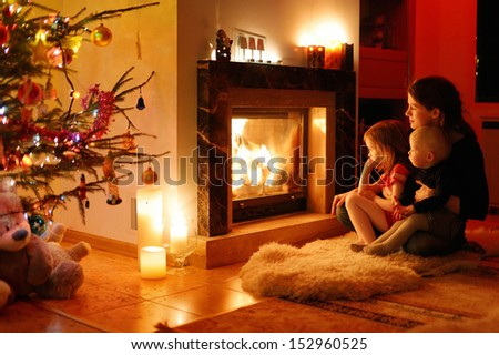 Young mother and her daughters by a fireplace on Christmas - stock photo