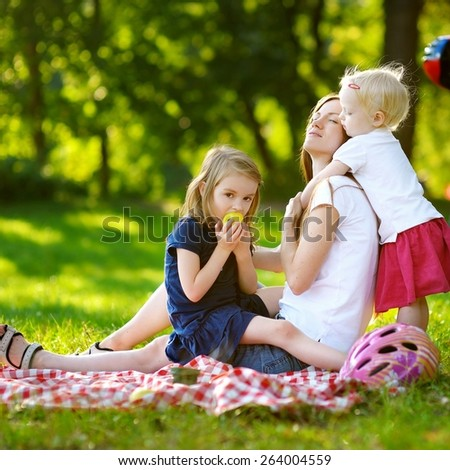Young mother and her daughters having a picnic in the park on beautiful summer day - stock photo