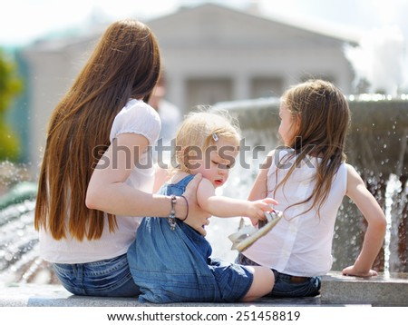 Young mother and her daughters having fun in a city fountain  - stock photo