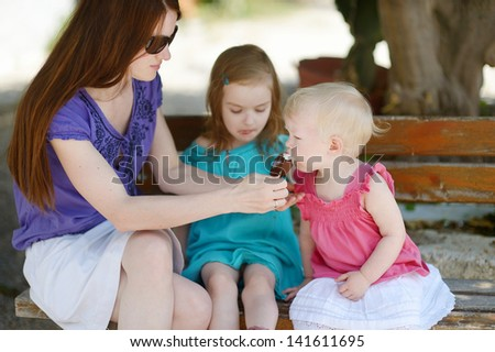 Young mother and her daugthters eating ice cream outdoors - stock photo