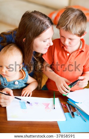 Young mother and her kids drawing together. Can be used also in kindergarten/daycare context. - stock photo
