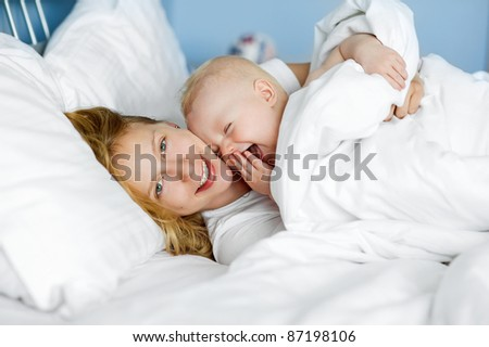 Young mother and her laughing baby - stock photo