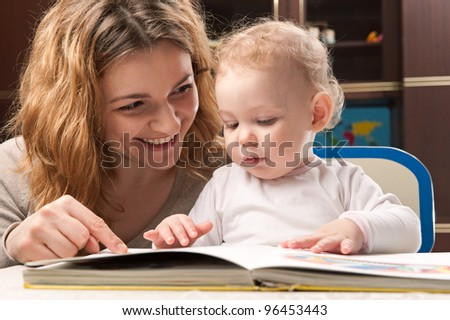 Young mother and her little baby daughter reading book - stock photo
