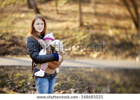 Young mother and her little baby in a carrier - stock photo