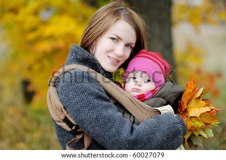 Young mother and her little baby in a carrier