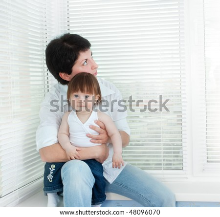 young mother and her little beautiful daughter sitting at the window