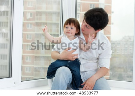 young mother and her little beautiful daughter sitting at the window - stock photo