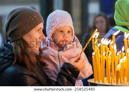Young mother and her little blond Caucasian daughter with candles in Orthodox Russian Church - stock photo