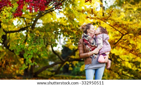 Young mother and her little daughter at beautiful autumn park. Kid girl and woman hugging and kissing. Family portrait outdoors. - stock photo