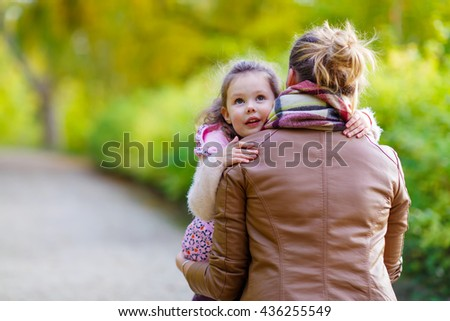 Young mother and her little daughter at beautiful autumn park. Kid girl and woman hugging and kissing. Lovely family portrait of two outdoors. - stock photo