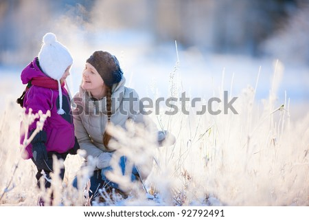 Young mother and her little daughter enjoying beautiful winter day outdoors - stock photo