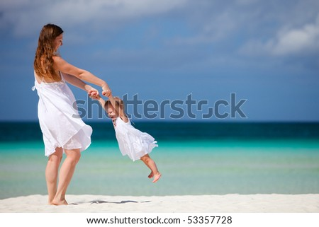 Young mother and her little daughter having fun on tropical white sand beach - stock photo