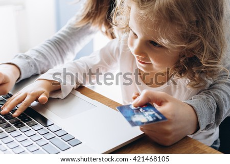 Young mother and her little daughter making online shopping - stock photo