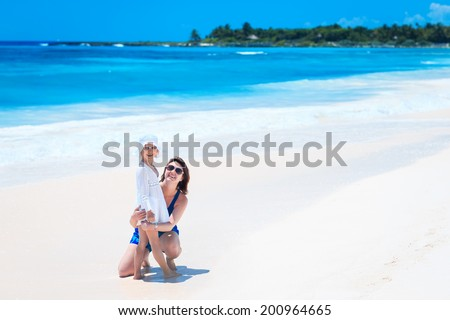 Young mother and her little daughter on tropical white sand beach - stock photo