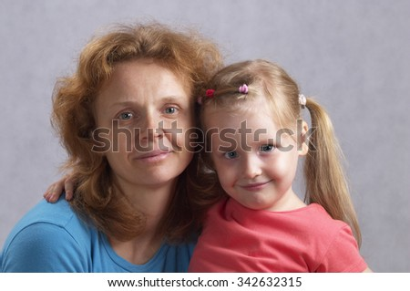 Young mother and her little daughter over defocused wallpaper background