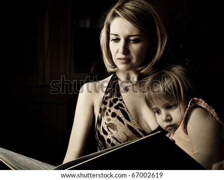 Young mother and her little daughter reading book before sleeping - stock photo