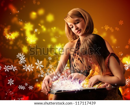 Young mother and her little daughter reading fairy book - stock photo