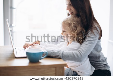 Young mother and her little daughter sitting using a laptop - stock photo