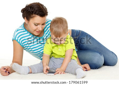 Young mother and her little son with mobile phone sit on a white background. Happy family.