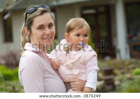 Young mother and her 9 months old babygirl in front of their home.