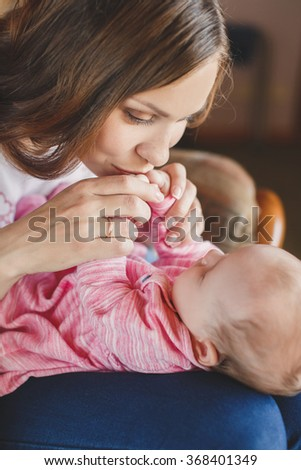 Young mother and her sleeping baby girl of 3 months. loving mother kissing her baby. Mom With her Child. Happy Family. woman with baby.  - stock photo