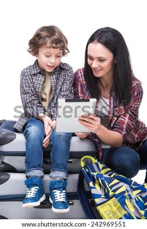 Young mother and her son are using tablet while sitting with luggage on the white background. - stock photo