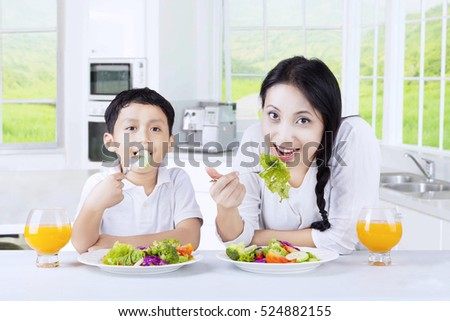 Young mother and her son eating fresh vegetables salad while drinking orange juice together in the kitchen
