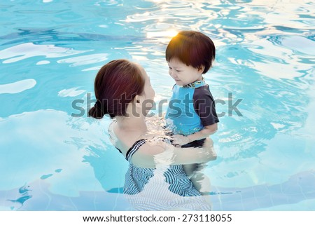 Young mother and her son having fun in a swimming pool - stock photo