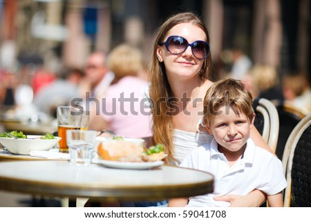Young mother and her son having lunch in outdoor restaurant on summer day