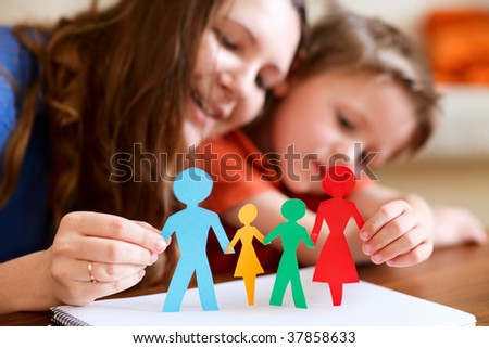 Young mother and her son holding figures of multicolored paper family - stock photo