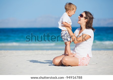 Young mother and her son playing happily at pretty beach
