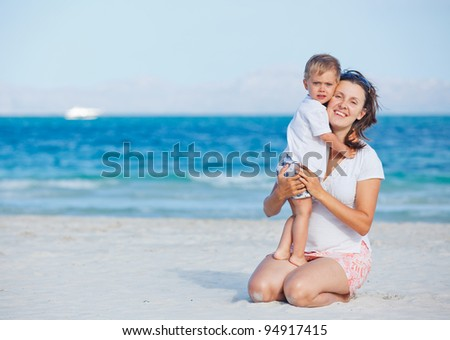 Young mother and her son playing happily at pretty beach - stock photo