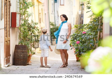 Young mother and her son playing outdoors in mediterranean city - stock photo