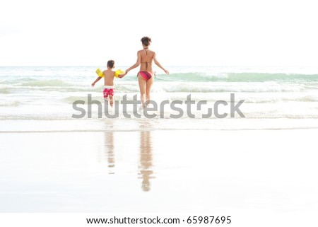 Young mother and her son running into water - stock photo