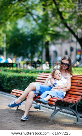 Young mother and her son sitting on bench in park - stock photo