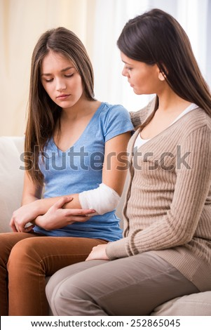 Young mother and her teen daughter with bandaging hand. - stock photo