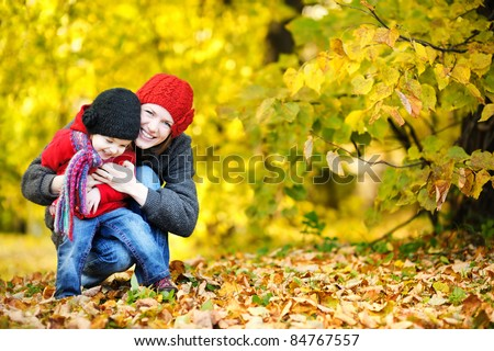 Young mother and her toddler girl have fun in autumn