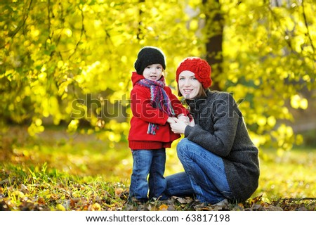 Young mother and her toddler girl in autumn fields
