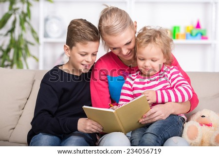 Young mother and her two children are reading a book together. Happy family.