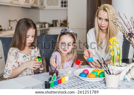 Young mother and her two daughters painting Easter eggs. Cozy home atmosphere. Easter - stock photo