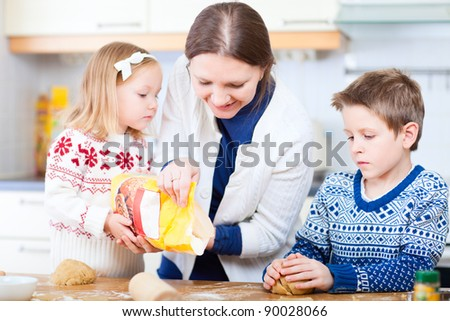 Young mother and her two kids at kitchen baking cookies - stock photo