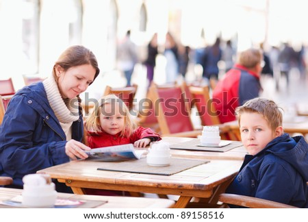 Young mother and her two kids at outdoor cafe on autumn day - stock photo