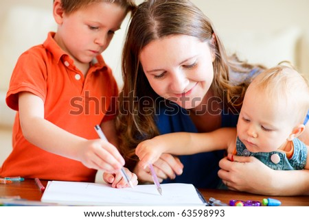 Young mother and her two kids drawing together - stock photo