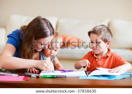 Young mother and her two kids drawing together. Can be used also in kindergarten/daycare context