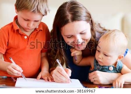 Young mother and her two kids drawing together. Can be used also in kindergarten/daycare context - stock photo