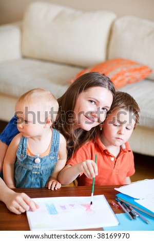 Young mother and her two kids drawing together. Can be used also in kindergarten/daycare context. - stock photo