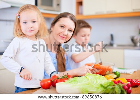 Young mother and her two kids making vegetable salad - stock photo