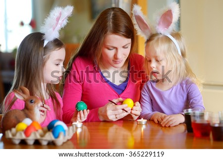 Young mother and her two little daughters painting colorful Easter eggs at home - stock photo