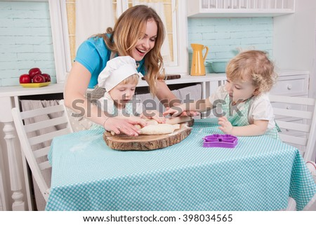 Young mother and her two small daughters in the kitchen