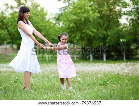 Young mother and her young daughter fun time together outdoors.